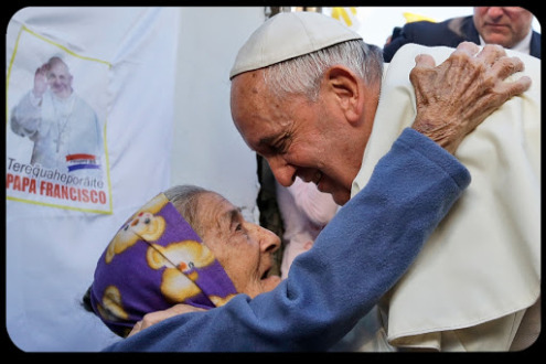 Pope Francis is greeted by a Catholic faithful during his visit to the Banado Norte neighborhood in Asuncion, on July 12, 2015. Pope Francis visted the poorest neighborhood of Paraguay before ending his Latin American tour. AFP PHOTO / POOL - GREGORIO BORGIA